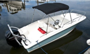Picture of repaired canvas Bimini top on a Boston Whaler super sport, tied to the dock in Miami Florida.