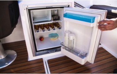 Picture of a mini boat fridge and freezer stocked with beer and water.