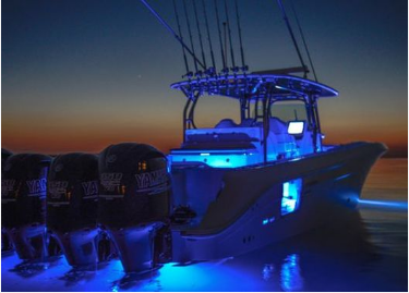 Picture of a center console fishing boat with blue LED deck light installed, glowing at night as the sun sets in Florida.