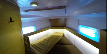 Picture of the v berth of a yacht with custom green color upholstery design with lounge.