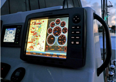 Picture of the dash of a fishing boat with a variety of digital displays showing engine and water information.