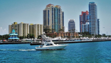 Photo of the Miami Harbor with the skyline in the background and a yacht passing by in August.