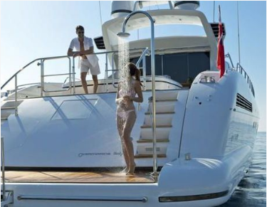 Picture of a woman showering on swim platform of a large yacht with an integrated shower system.
