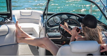Woman relaxing in the helm seat of a cleaned boat with a beverage in hand off the cost of Miami.