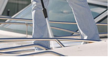 A trained boat cleaner spraying down the top deck of a yacht in Miami.