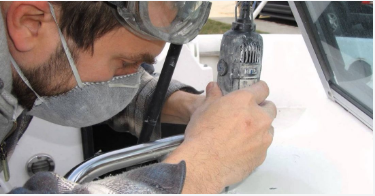 Yacht repair professional uses a dremel to precisely cut away and replace damaged fiberglass on a boat.
