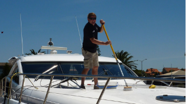 Picture of yacht cleaning service scrubbing the bow of yacht in Florida.