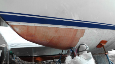 Fiberglass expert cuts away old worn hull bottom to be replaced with new fiberglass layers and gelcoat.
